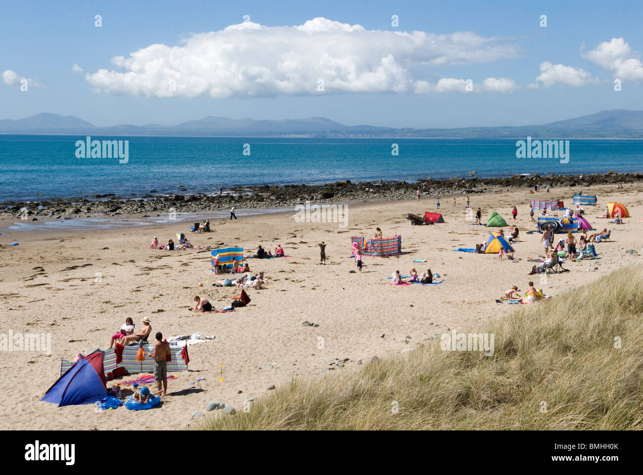 Llandanwg beach with summer holidaymakers. Gwynedd North Wales UK. Snowdonia National Park in distance. - Stock Image