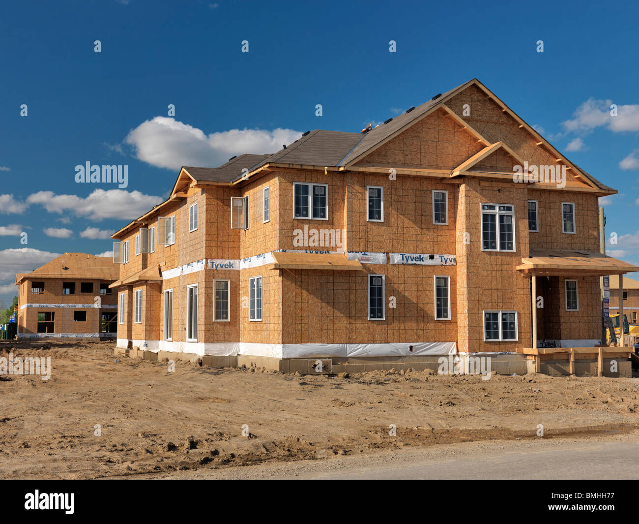 Wooden frame two story house with osb sheathed walls under for Complete home construction