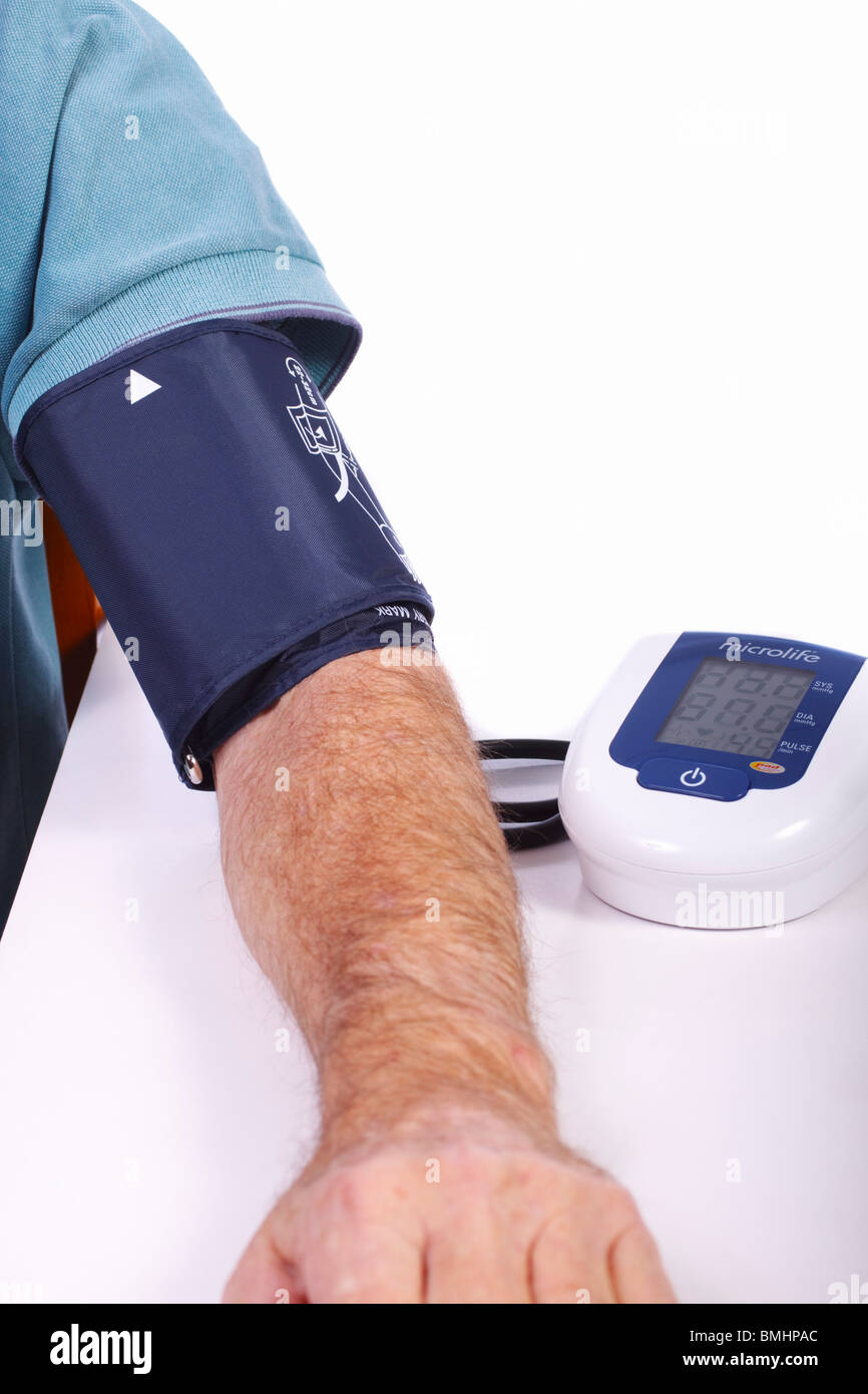 Male with blood pressure meter attached to his arm. - Stock Image