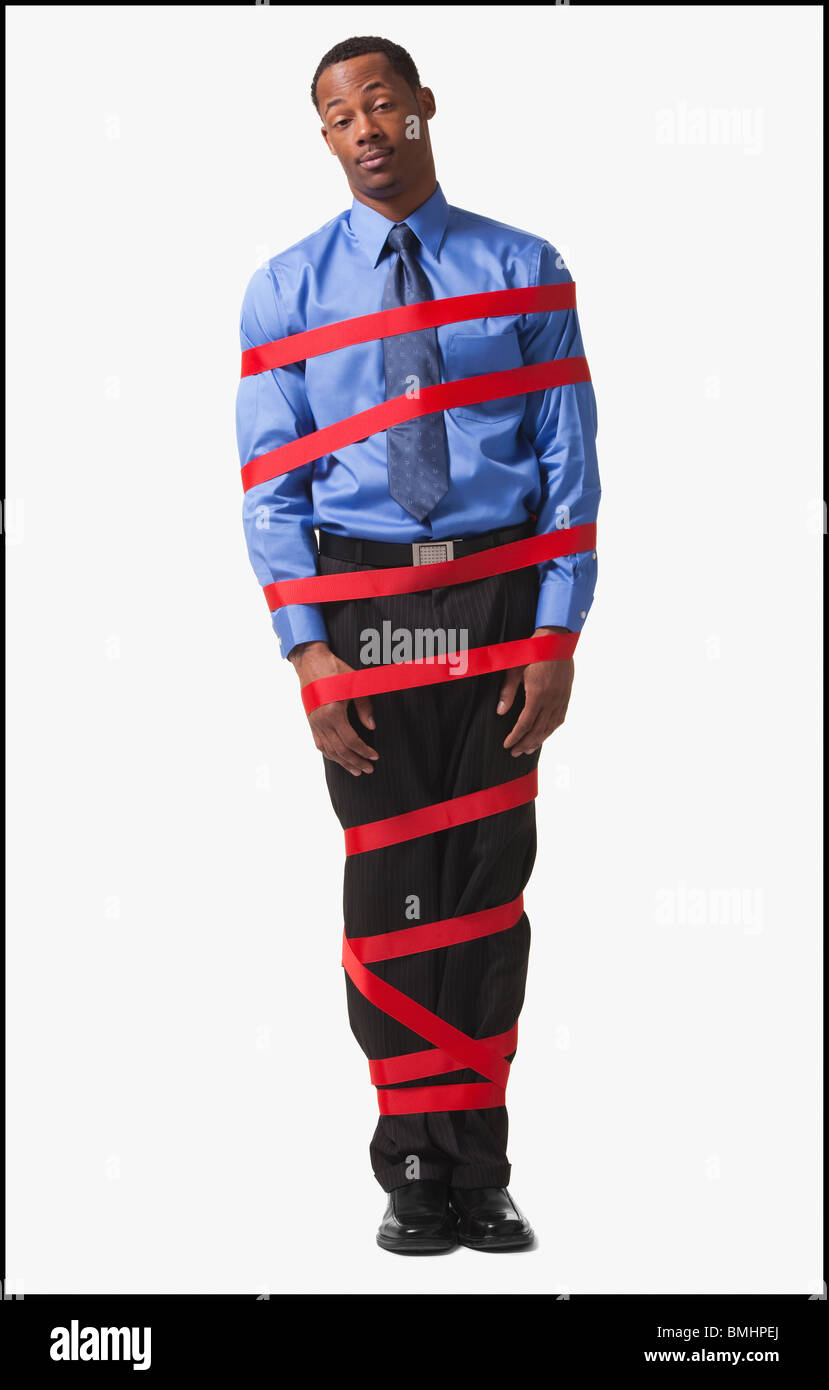 Businessman wrapped in red tape - Stock Image