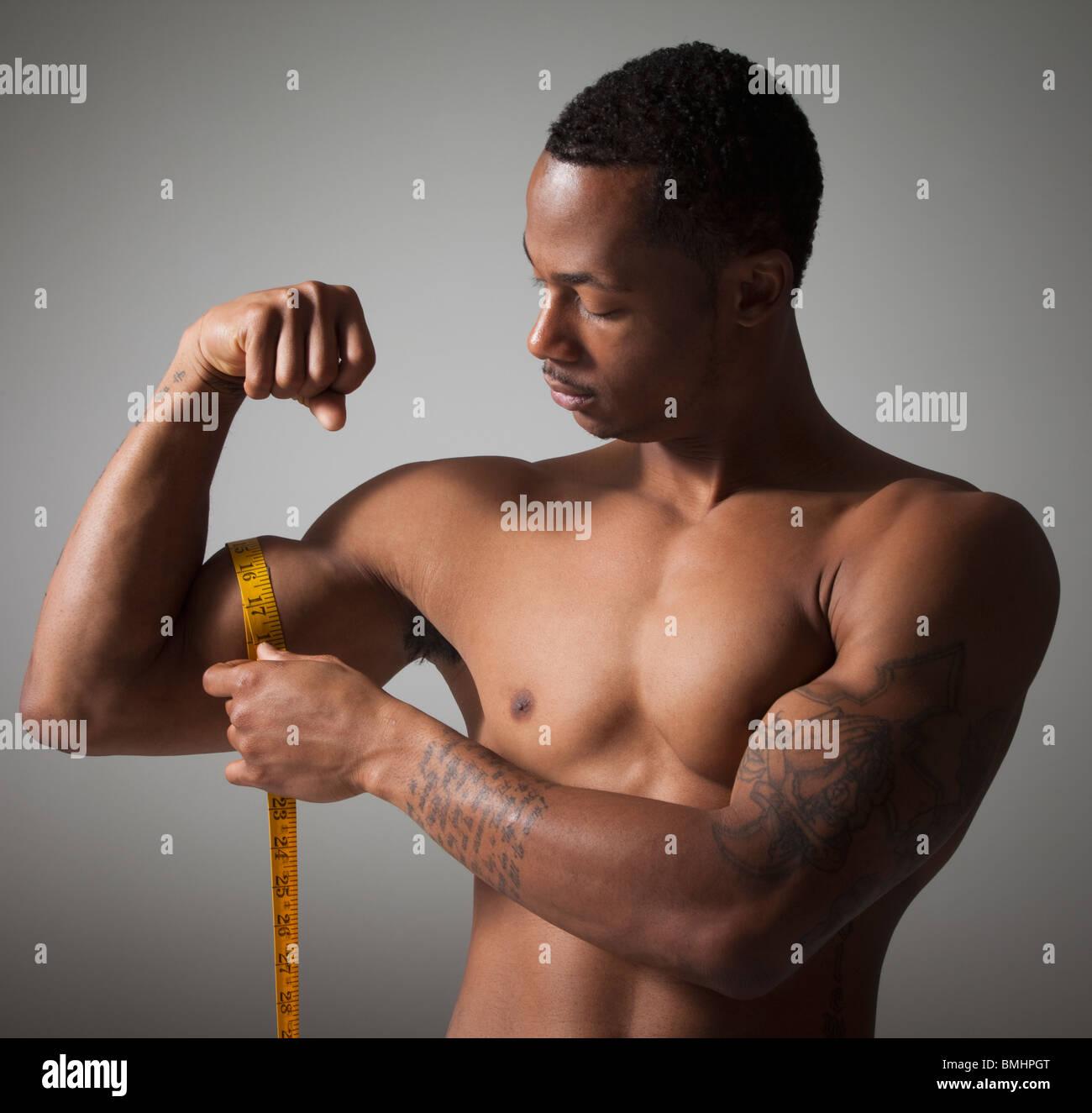 Man measuring his triceps - Stock Image