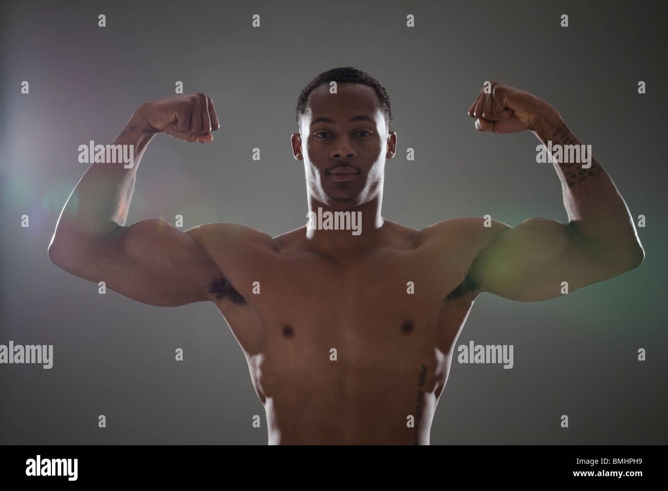 Physically fit man flexing his triceps - Stock Image