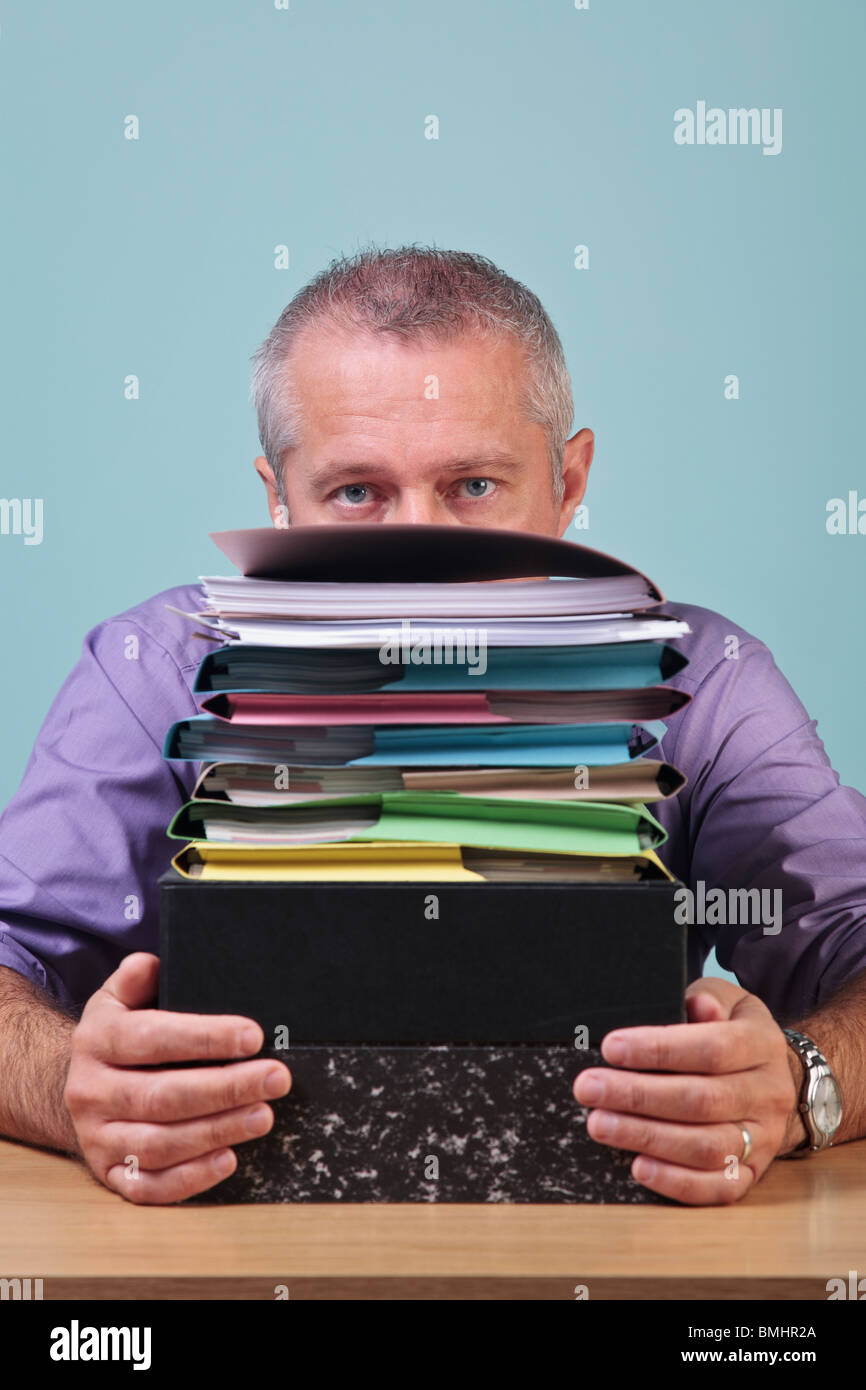 Man sitting behind a stack of paper work - Stock Image