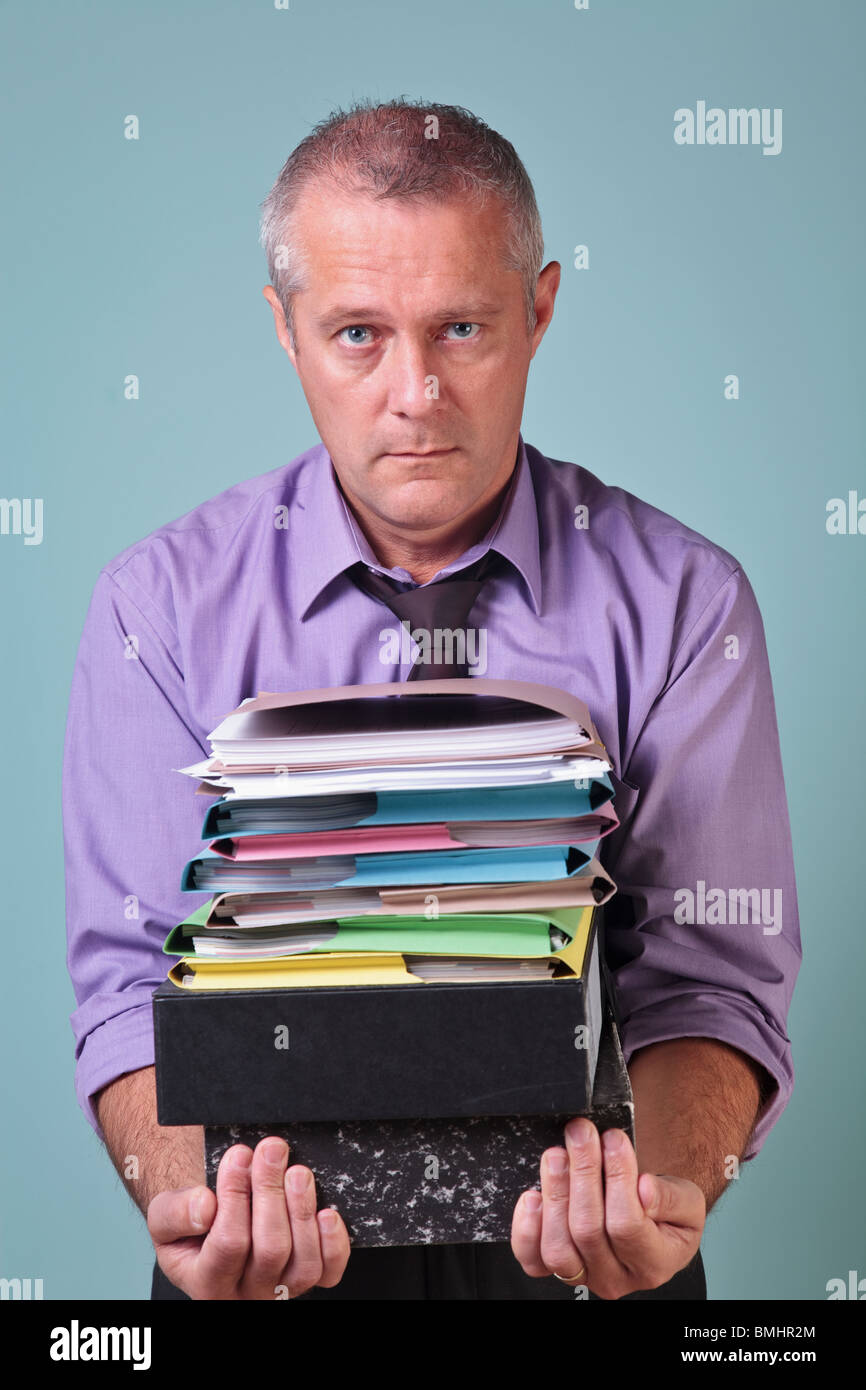 Man holding a stack of paper work - Stock Image