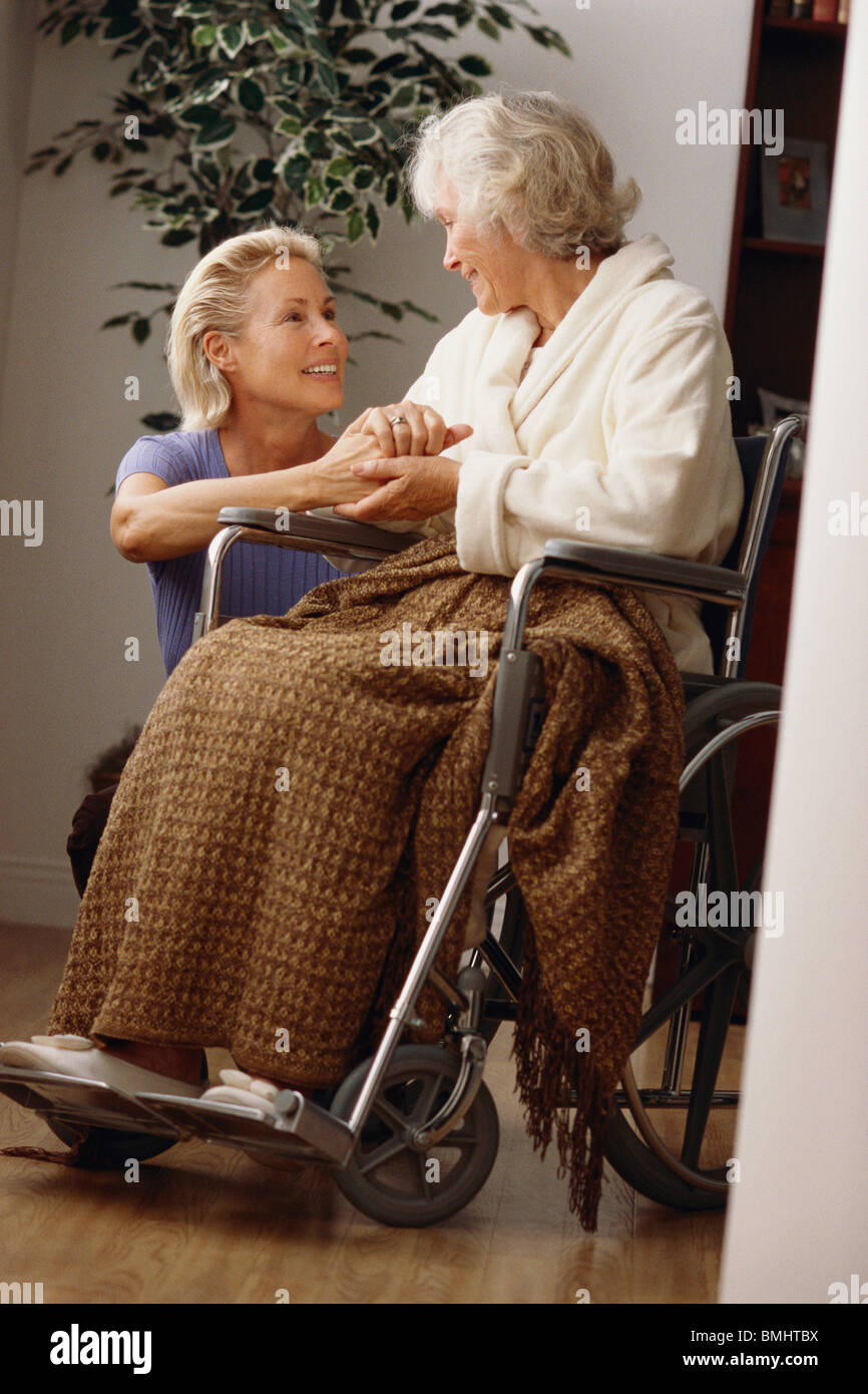 Attendant comforting an elderly woman in a wheelchair - Stock Image