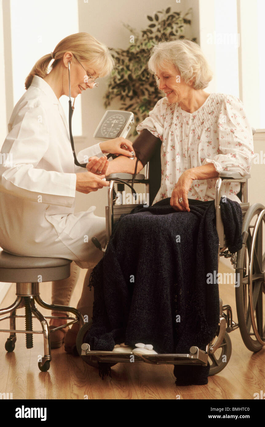 Healthcare worker checking an elderly woman's blood pressure - Stock Image