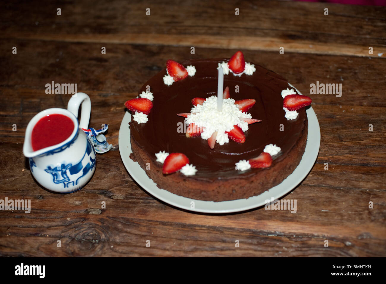 Chocolate Strawberry Birthday Cake With One Candle And A Delfts Blue Jar Of Sauce