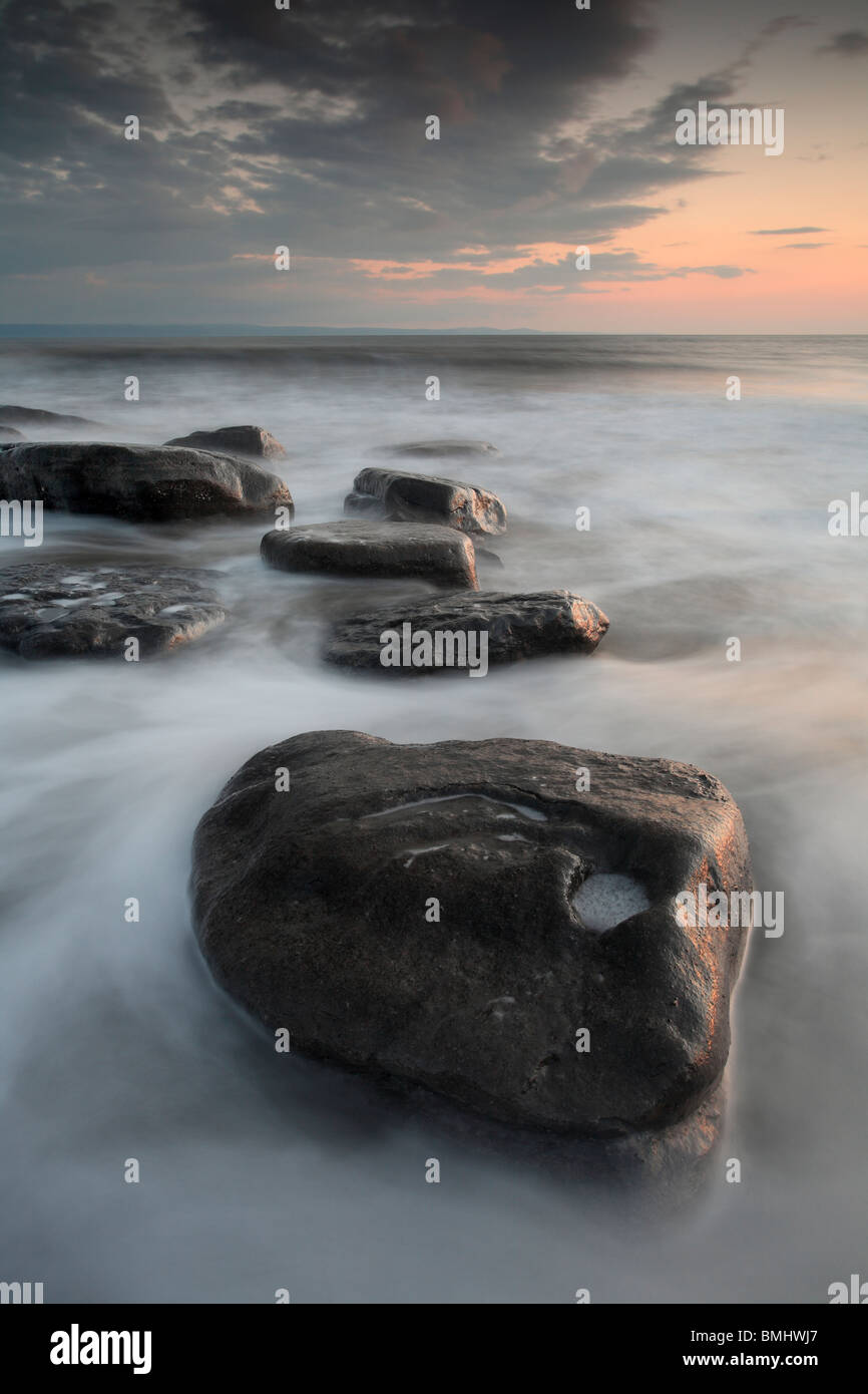 An incoming tide washes amidst the rocks at Dunraven Bay near Southerndown, Wales - Stock Image