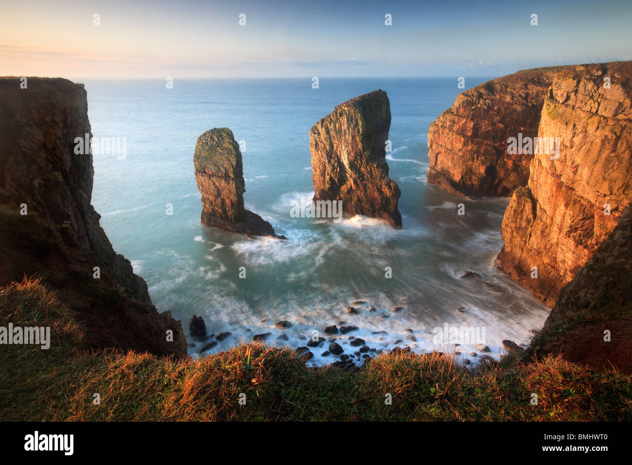The Elegug Stacks at dawn on a winter's morning along the Pembrokeshire Coast Path in Wales - Stock Image