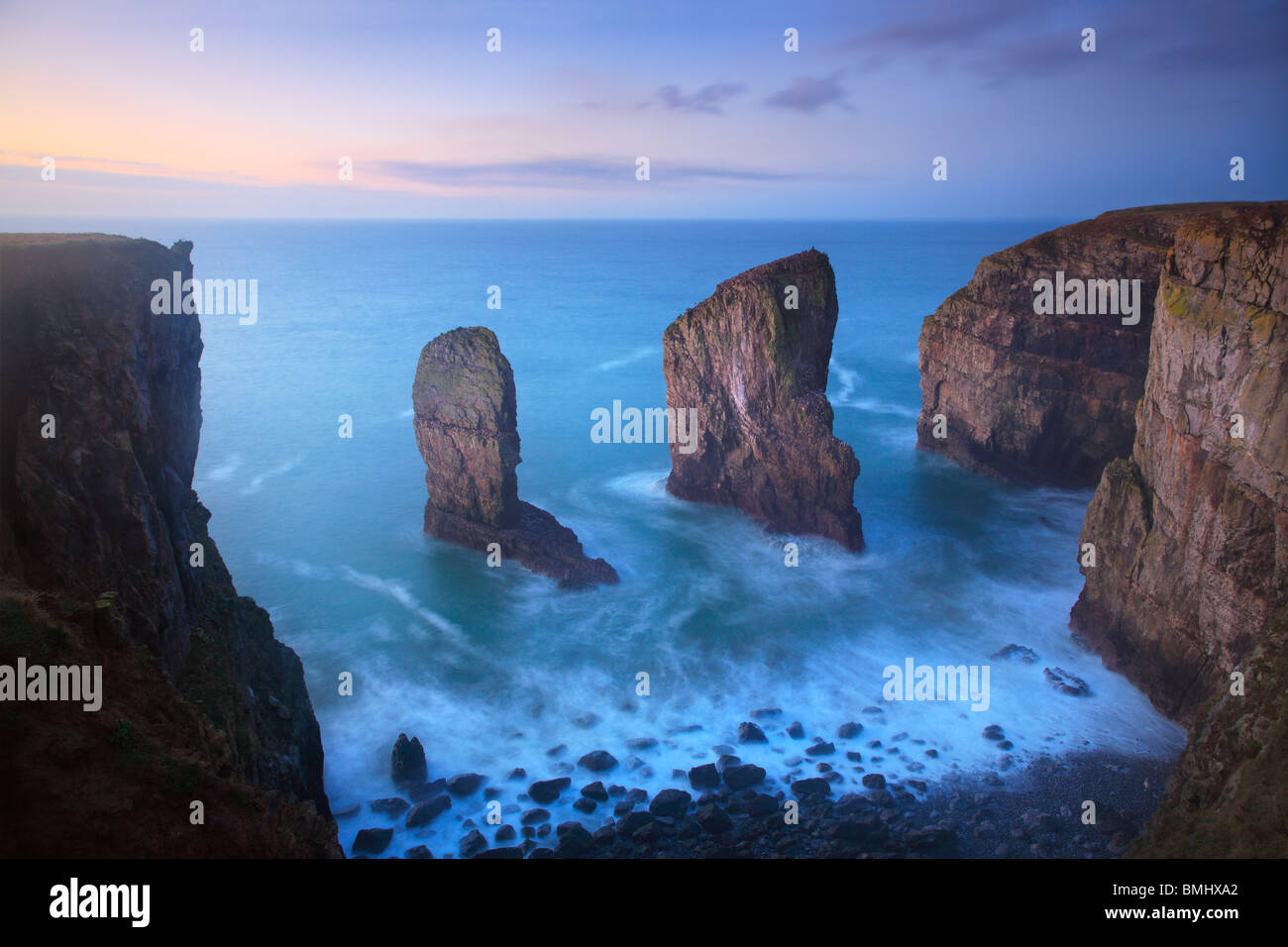 The Elegug Stacks just before dawn on a winter's morning along the Pembrokeshire Coast Path in Wales - Stock Image