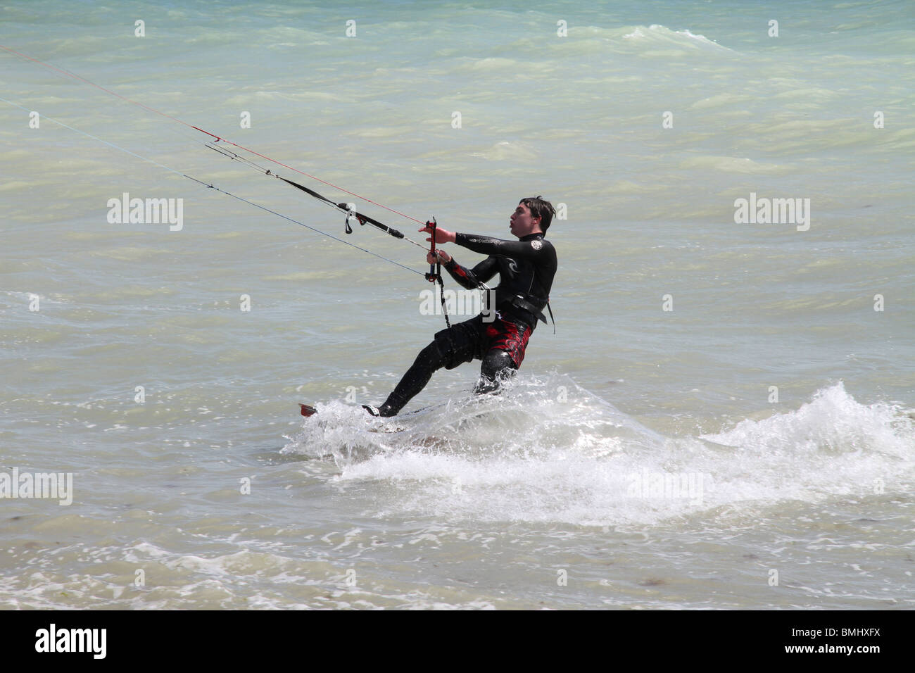 Para surfer in the sea at Worthing grunting with effort. - Stock Image