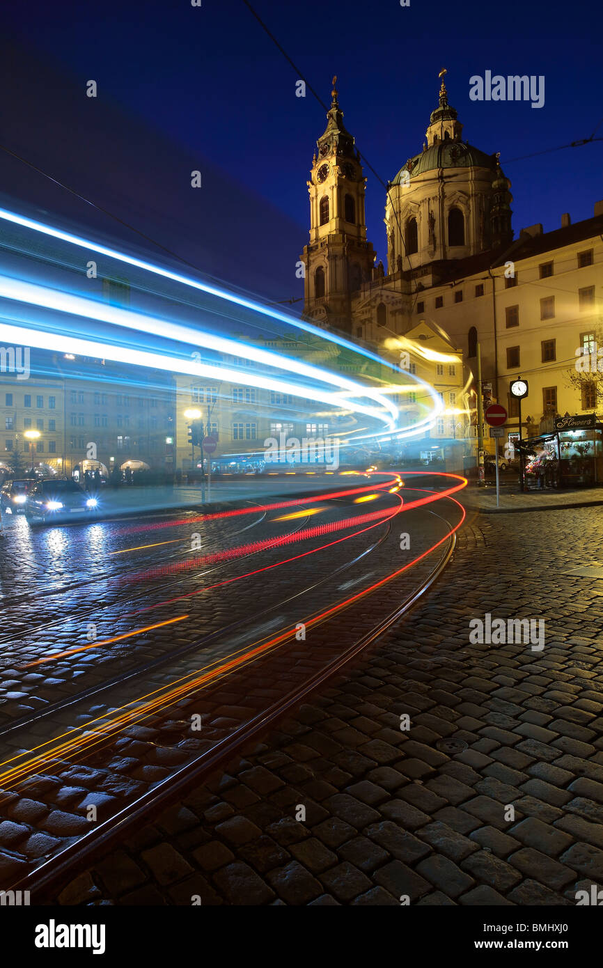 Light trails from a streetcar (Tramvaj) pulling into a stop in front of St Nicholas Cathedral in Lesser Town, Prague - Stock Image