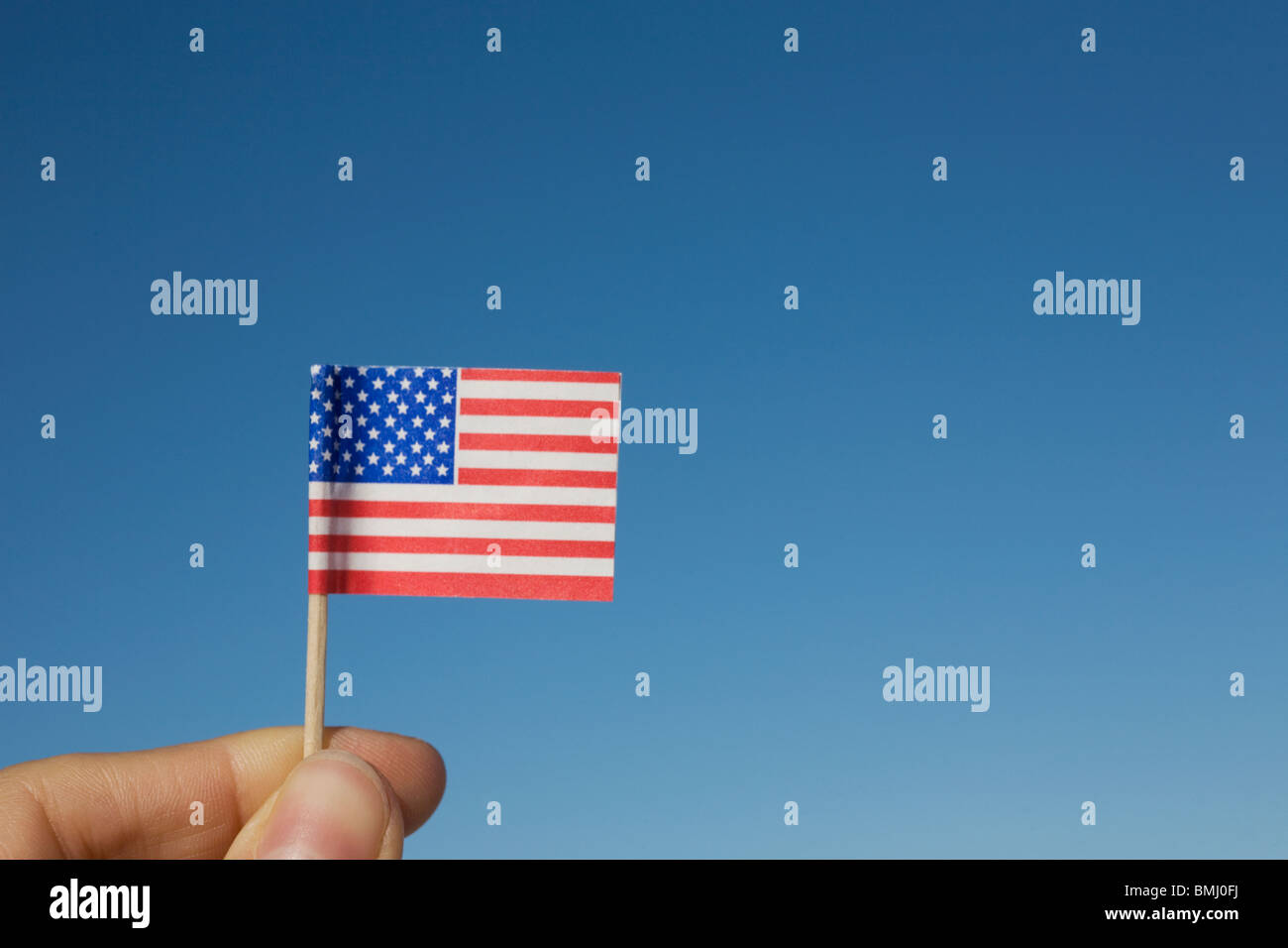 Hand holding small American flag - Stock Image