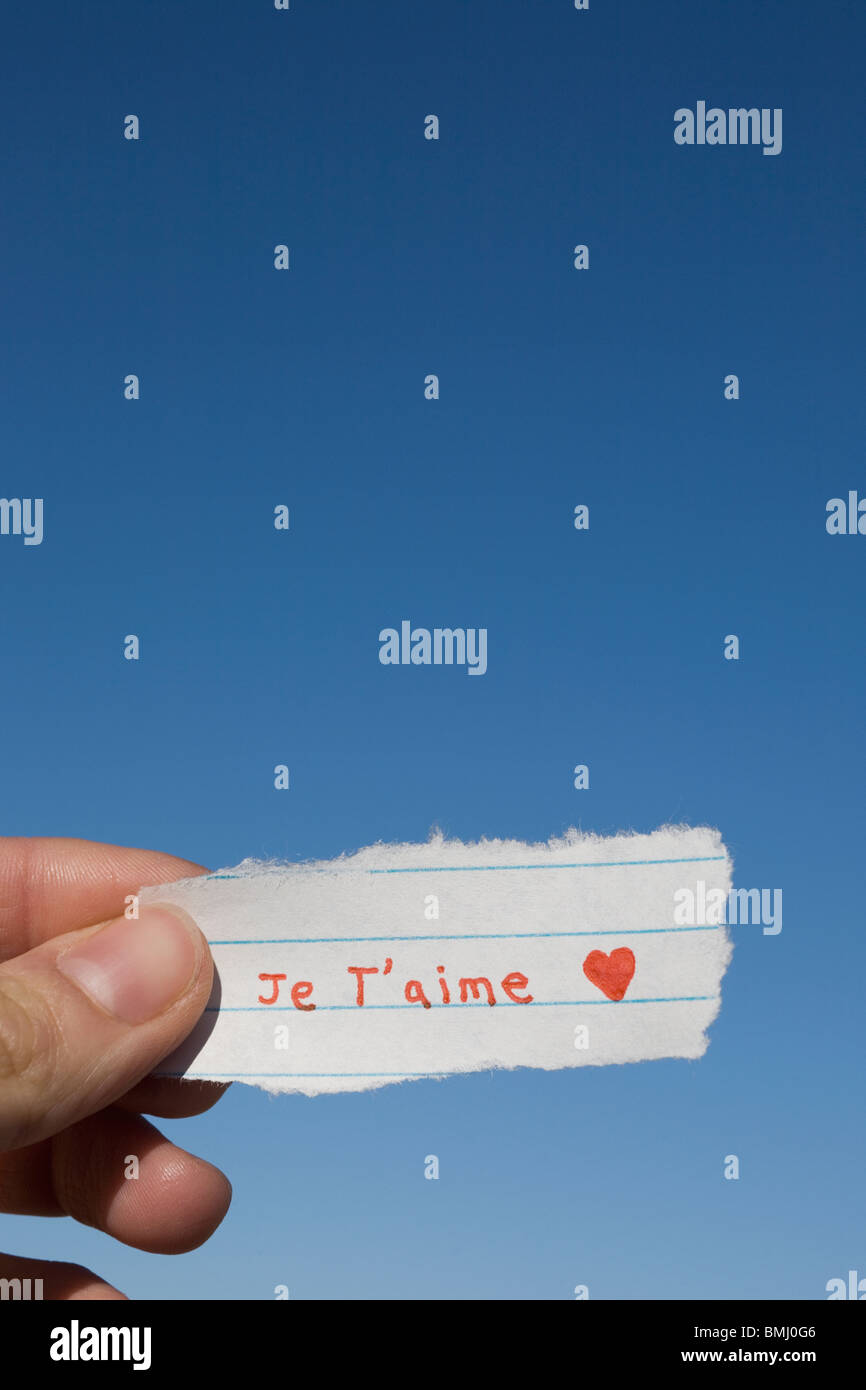 Hand holding I love you note written in French - Stock Image