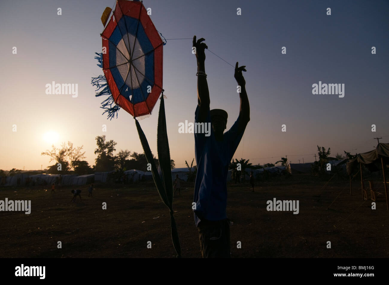 Young boy playing with a kite at a makeshift camp for survivors of a 7.0 magnitude earthquake which struck Haiti - Stock Image