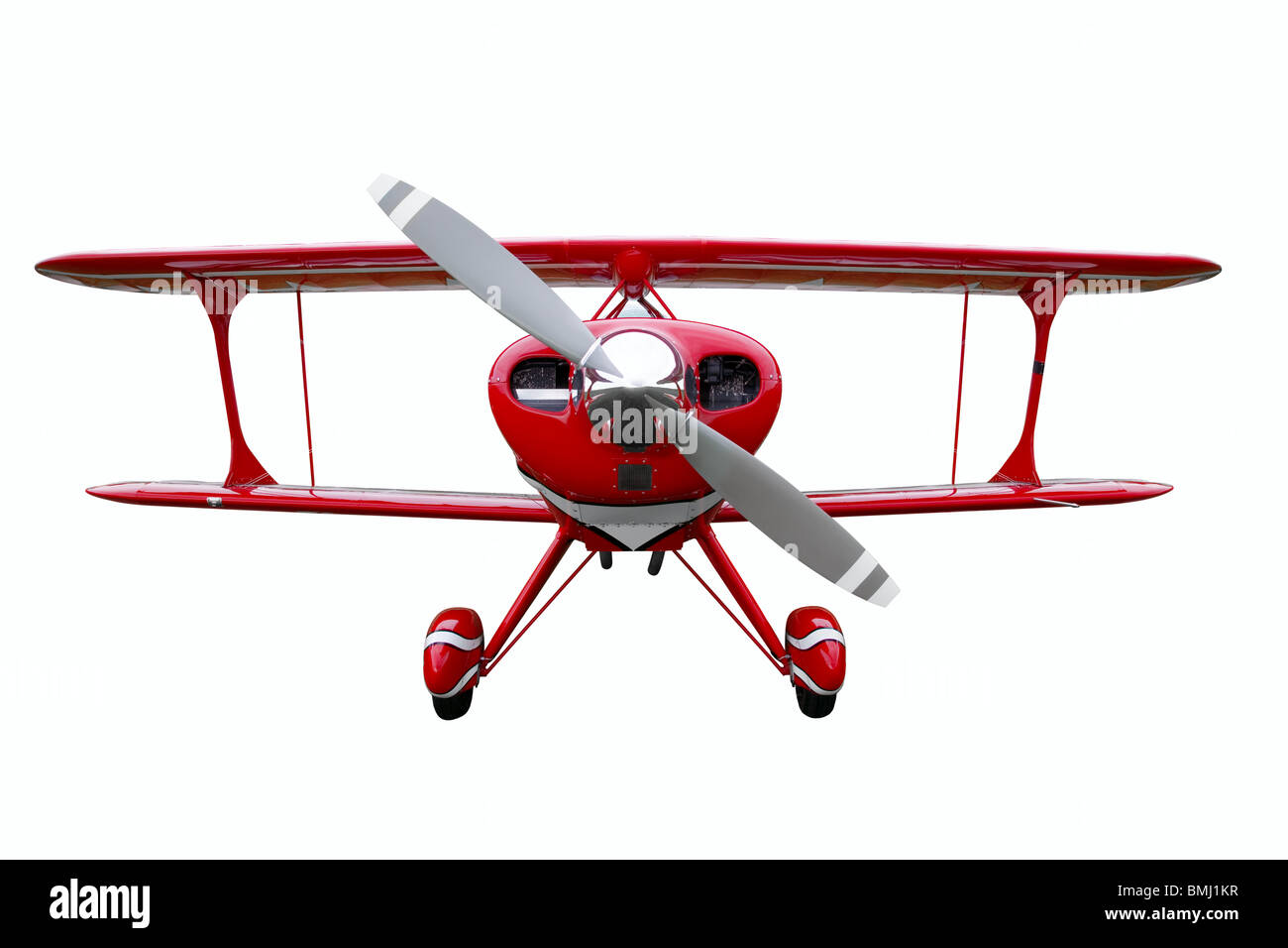 A red biplane isolated on a white background. - Stock Image