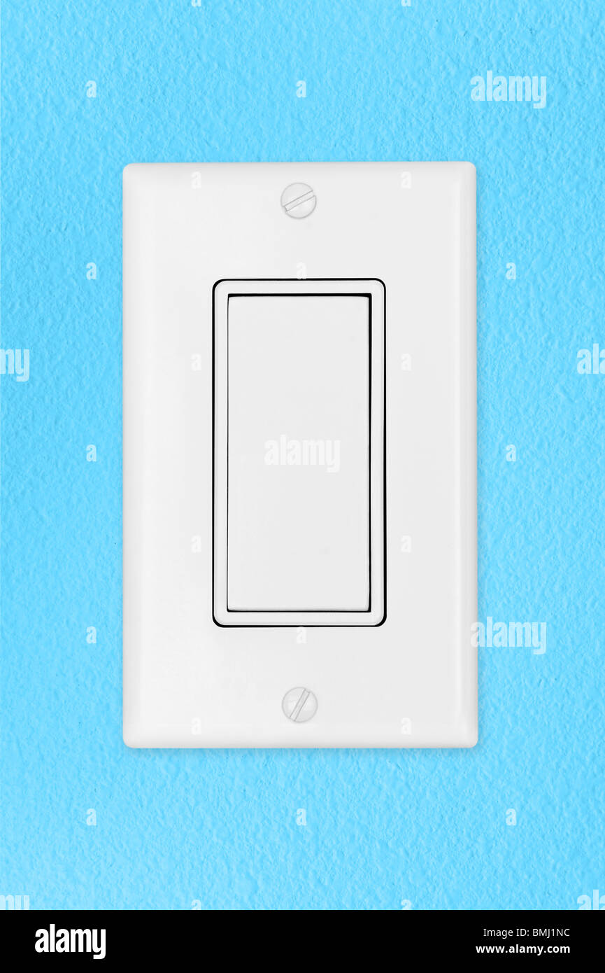 A modern toggle electrical light switch on a blue wall - Stock Image