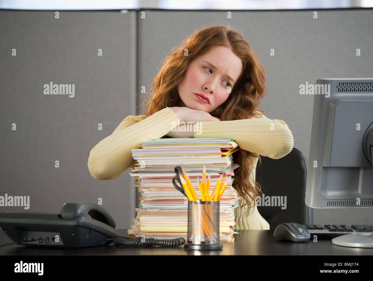 Overworked woman in cubicle - Stock Image