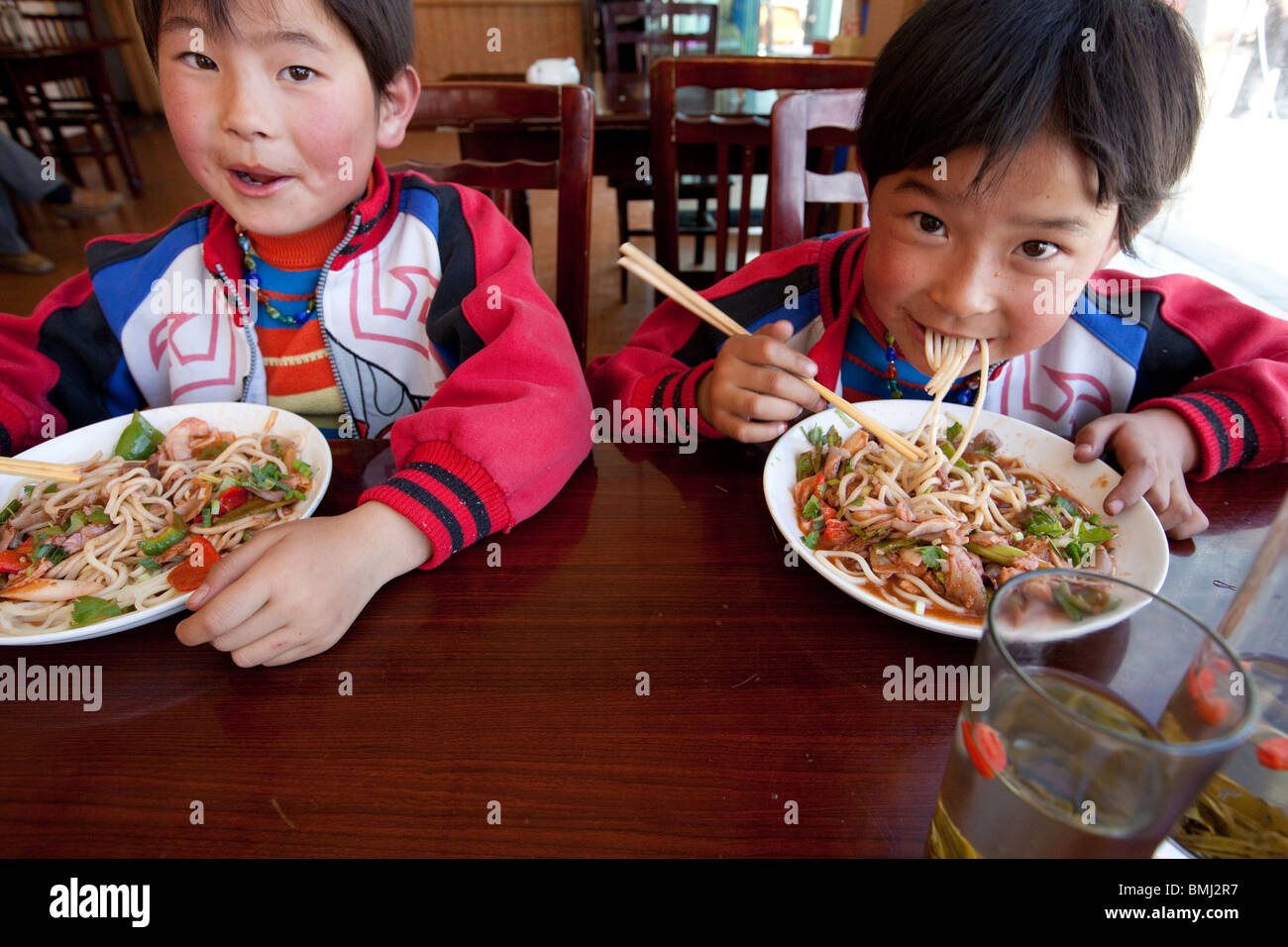 Brothers eating noodles in Shigatse, Tibet Stock Photo