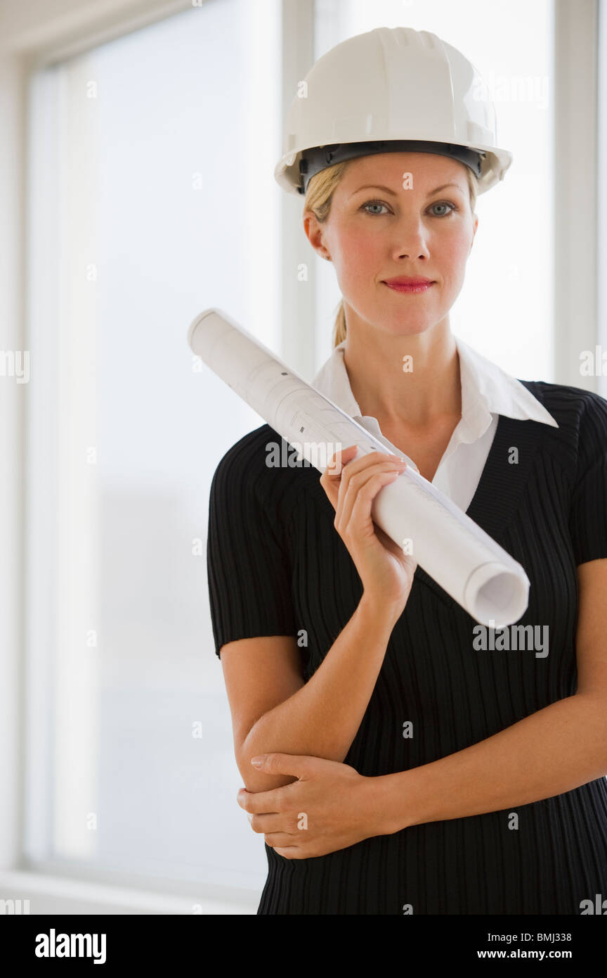 Female architect holding blueprints - Stock Image