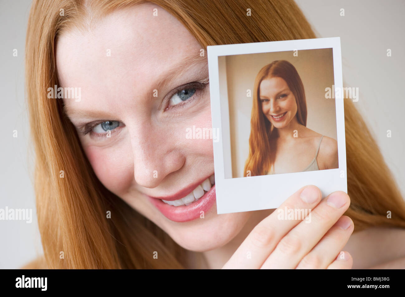 Woman holding a photograph of herself - Stock Image