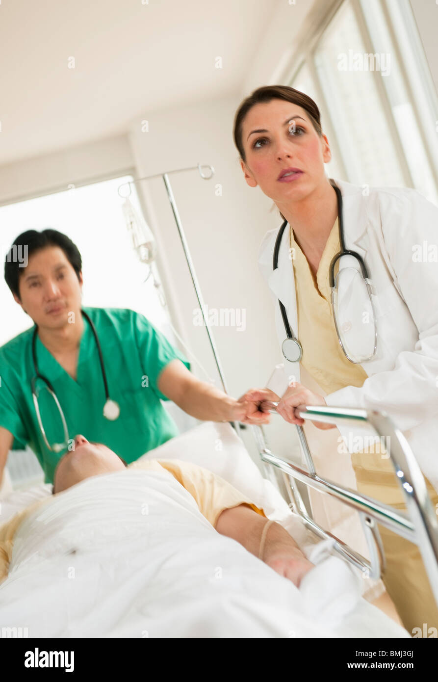 Healthcare workers pushing gurney in emergency room - Stock Image