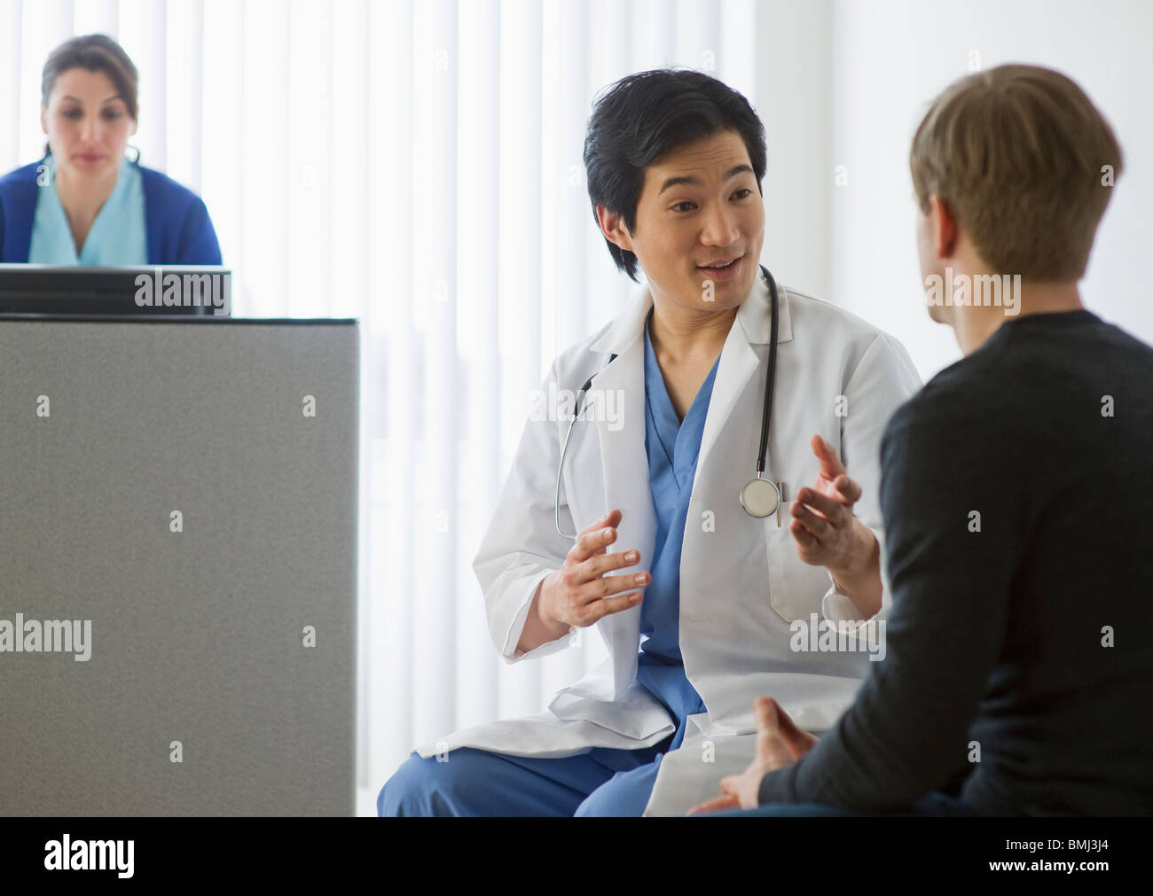 Doctor talking to patient in waiting room - Stock Image