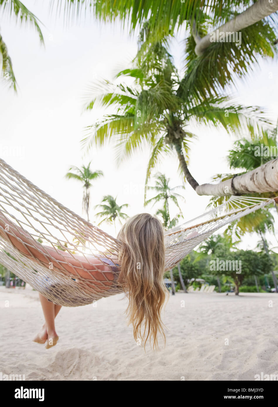 Blonde woman relaxing in hammock - Stock Image