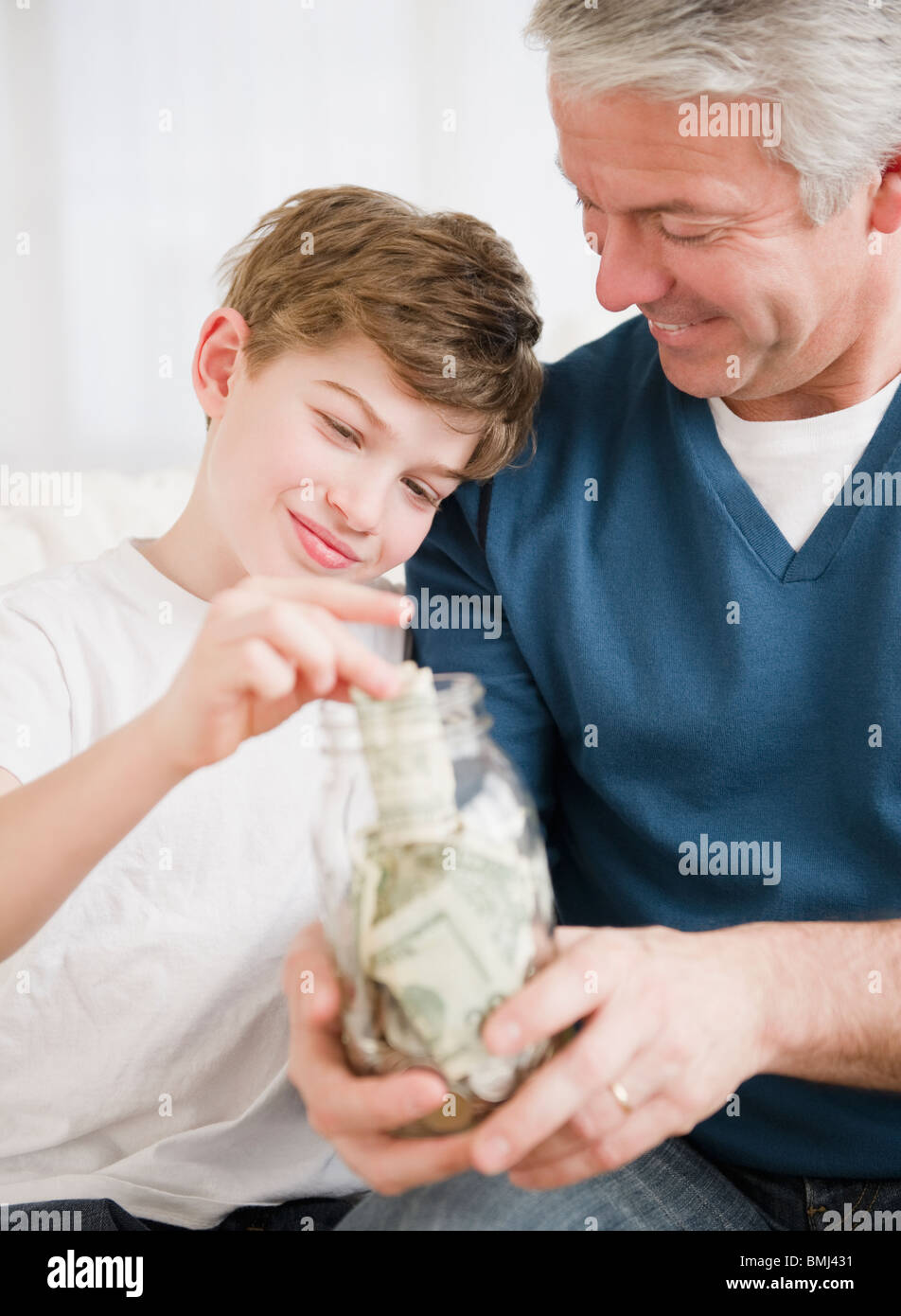 Father and son putting money in jar - Stock Image