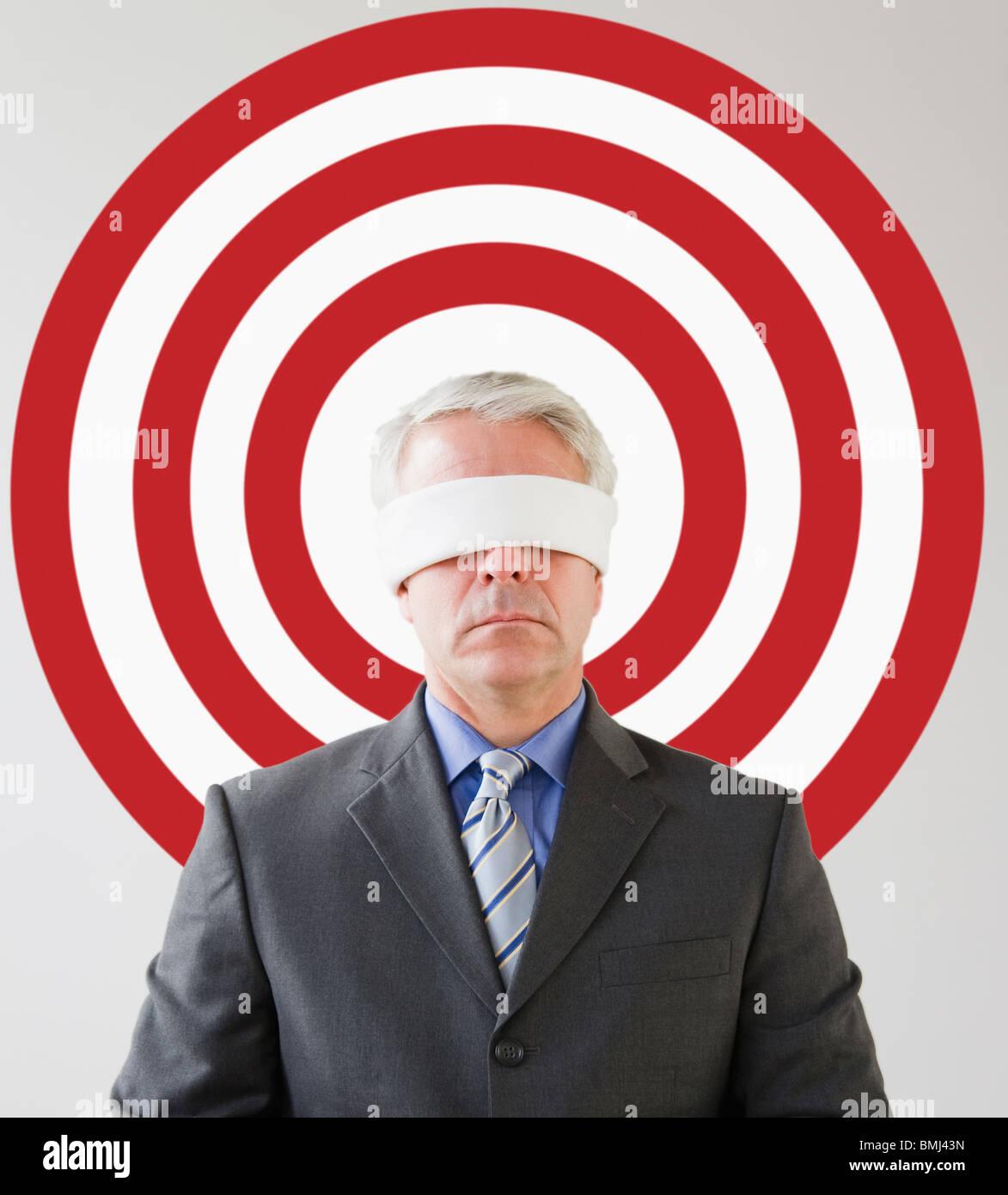 Blindfolded man standing in front of bull's eye - Stock Image