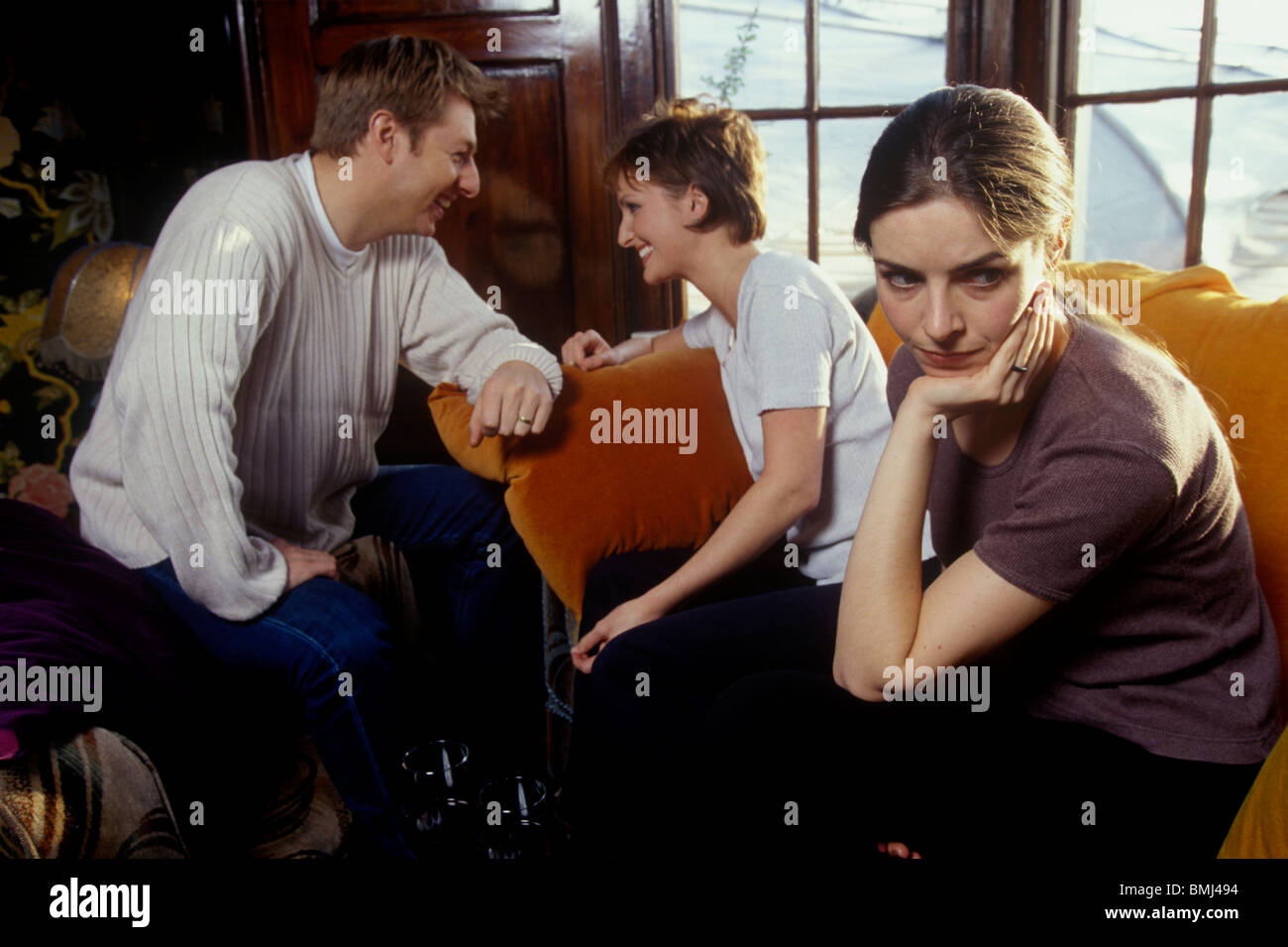 a couple having a drink together in a bar with a woman in the foreground looking fed up - Stock Image