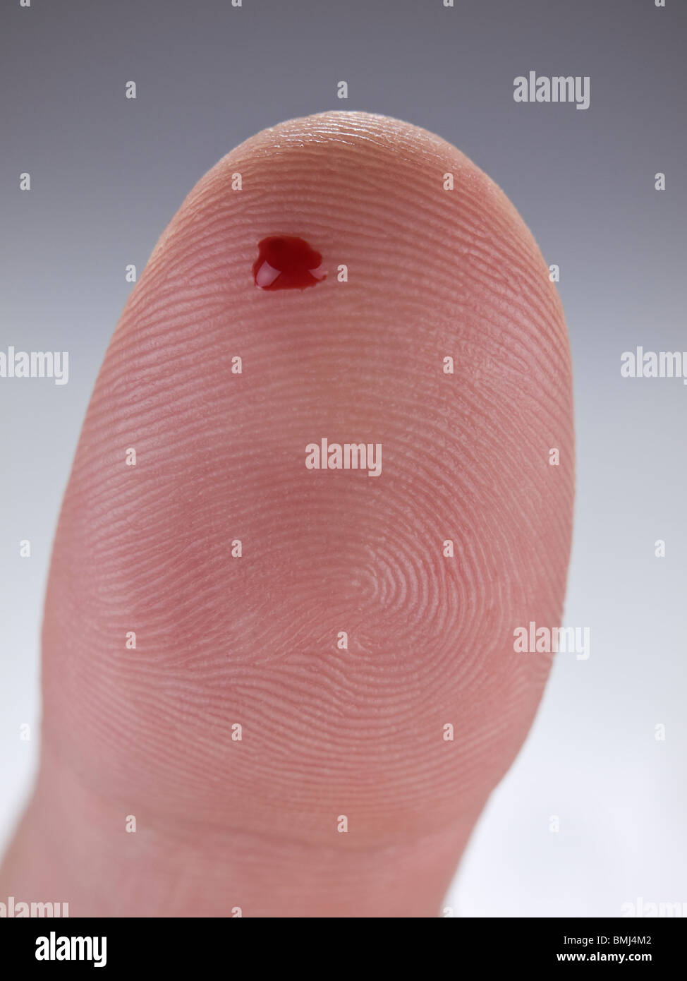 Macro view of a drop of real blood on a human thumb. - Stock Image