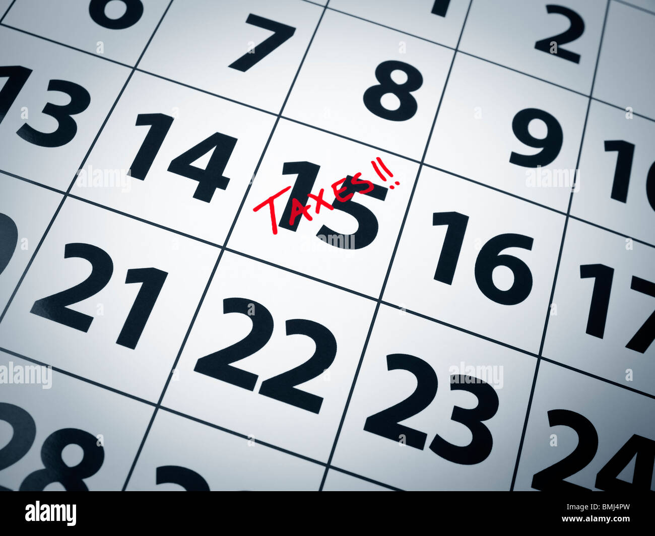 Taxes written in red on the 15th day of a calendar. - Stock Image