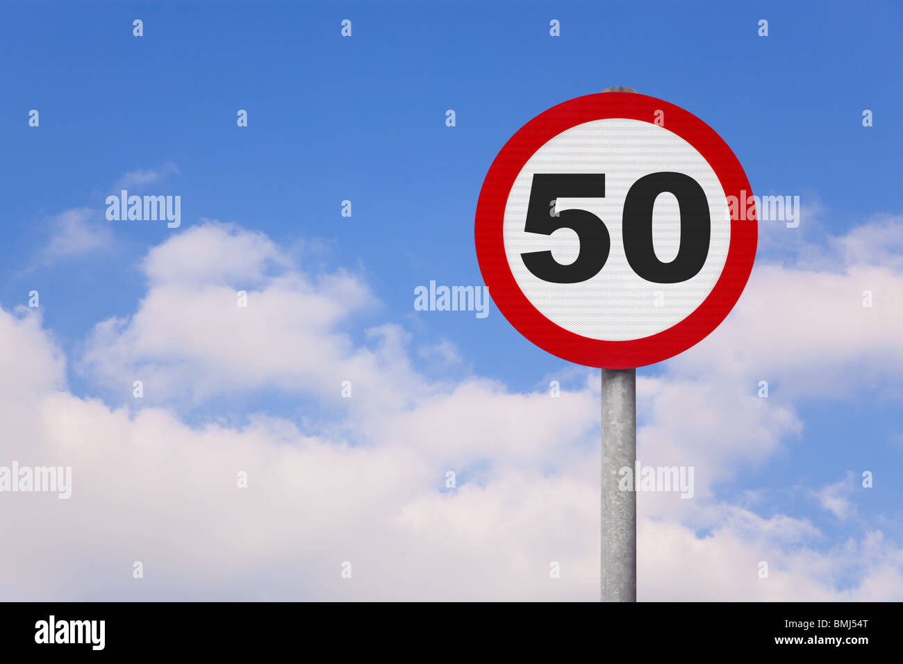A round roadsign with the number 50 on it against a blue cloudy sky. - Stock Image