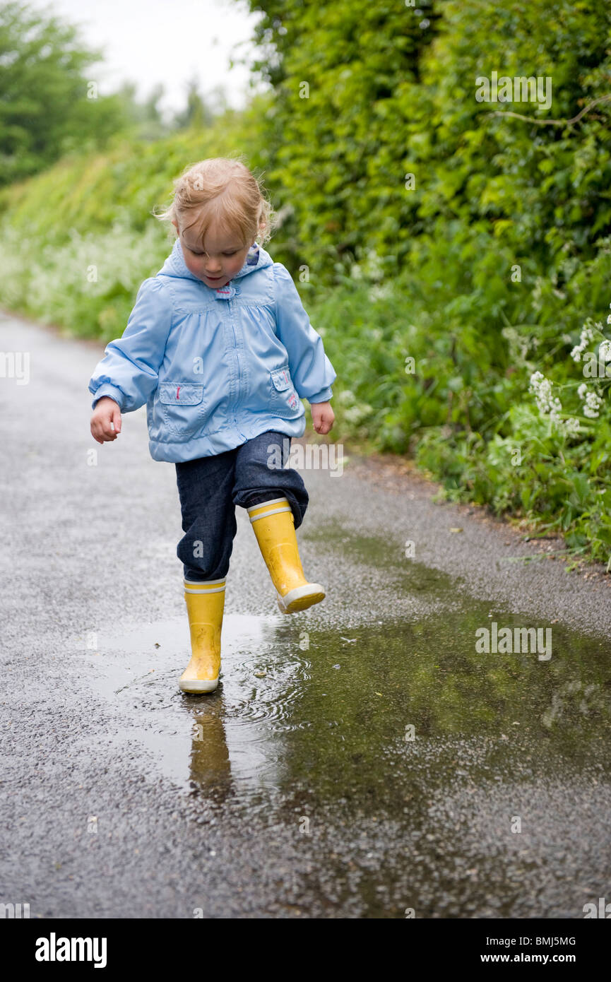 GIRL TODDLER PLAYS IN PUDDLES IN WET WEATHER - Stock Image