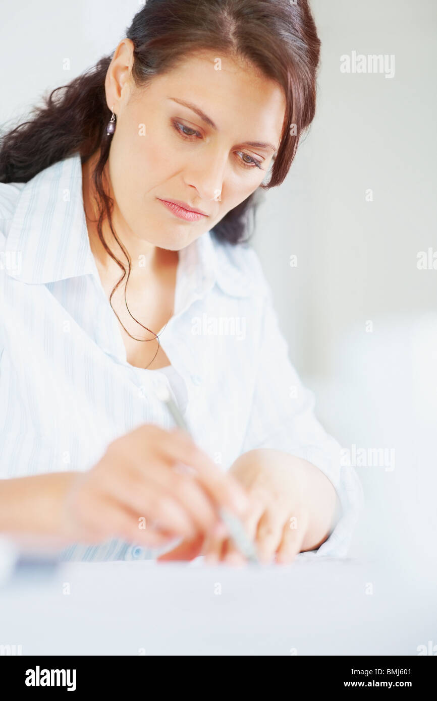 Woman looking at blueprints - Stock Image
