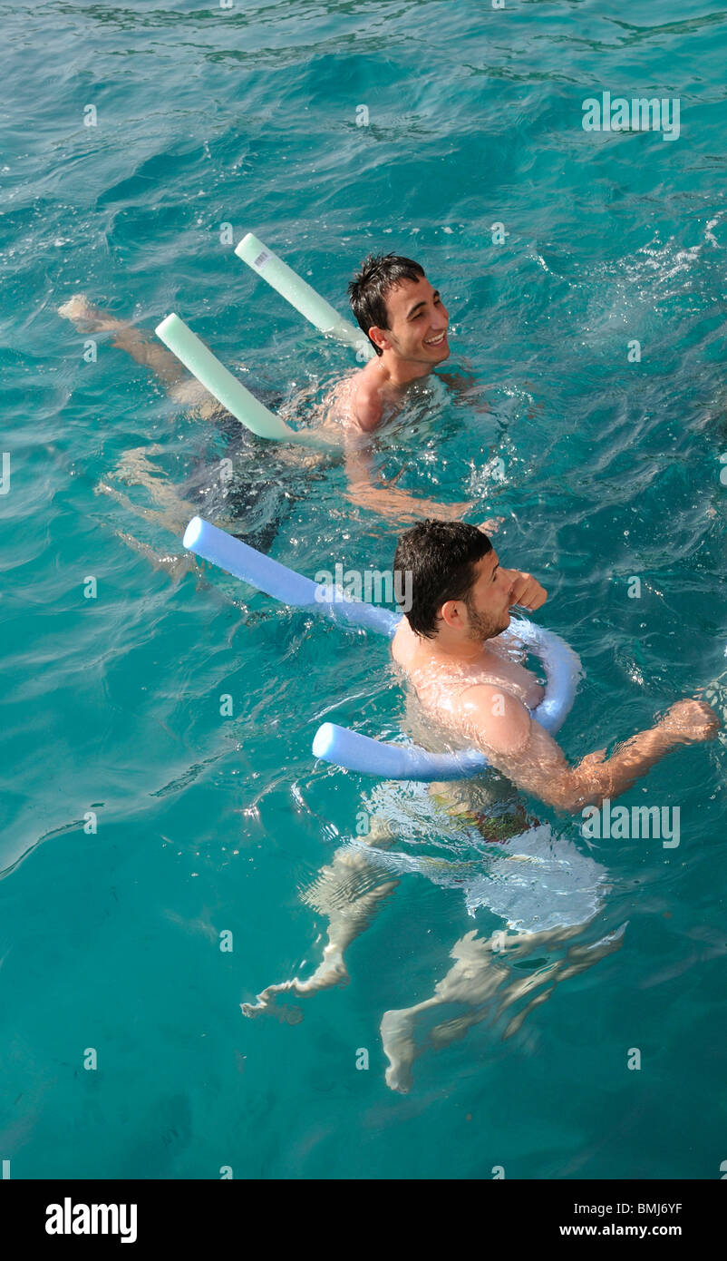 5d5615767 Young men using a swimming noodles as a buoyancy aid as they swim in the  Aegean