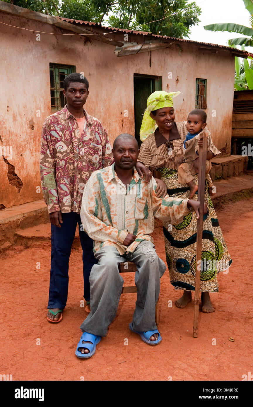 Rwandan family out side home. Father is disabled and uses a crutch. Rwanda - Stock Image