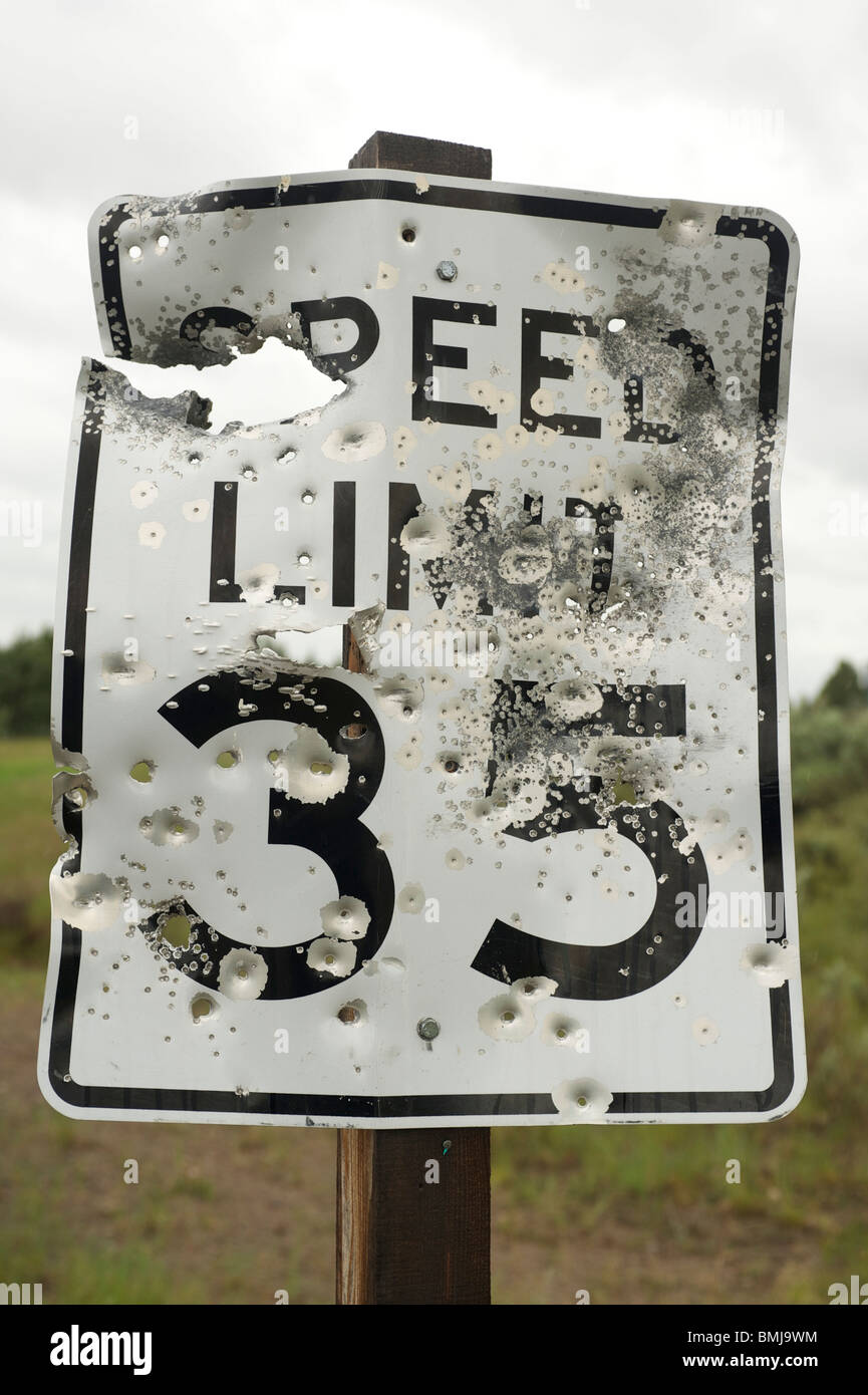Bullet scarred and shot out road sign. Idaho USA - Stock Image