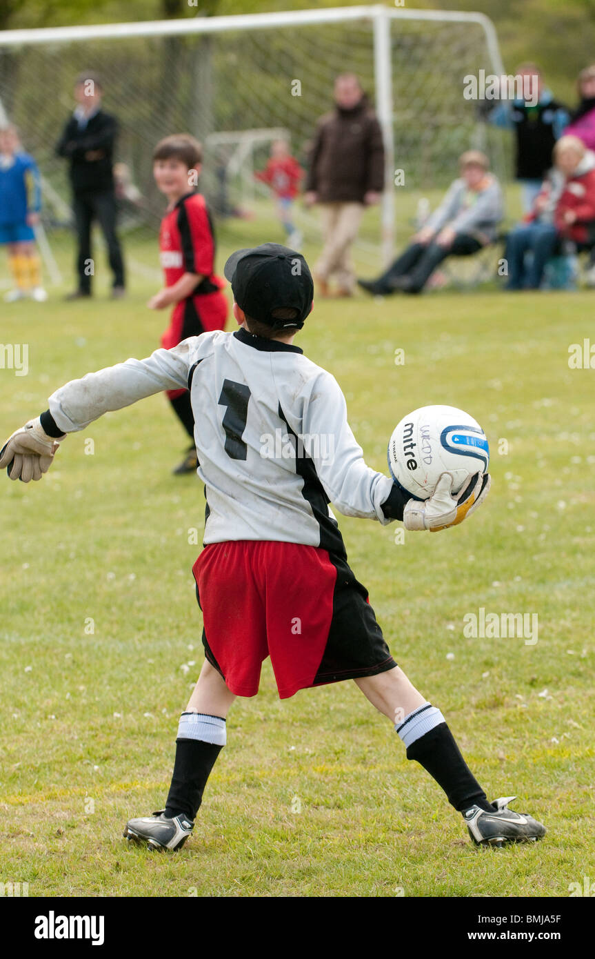 Goalkeeper throwing the ball - teenage boys playing football soccer game sports UK - Stock Image