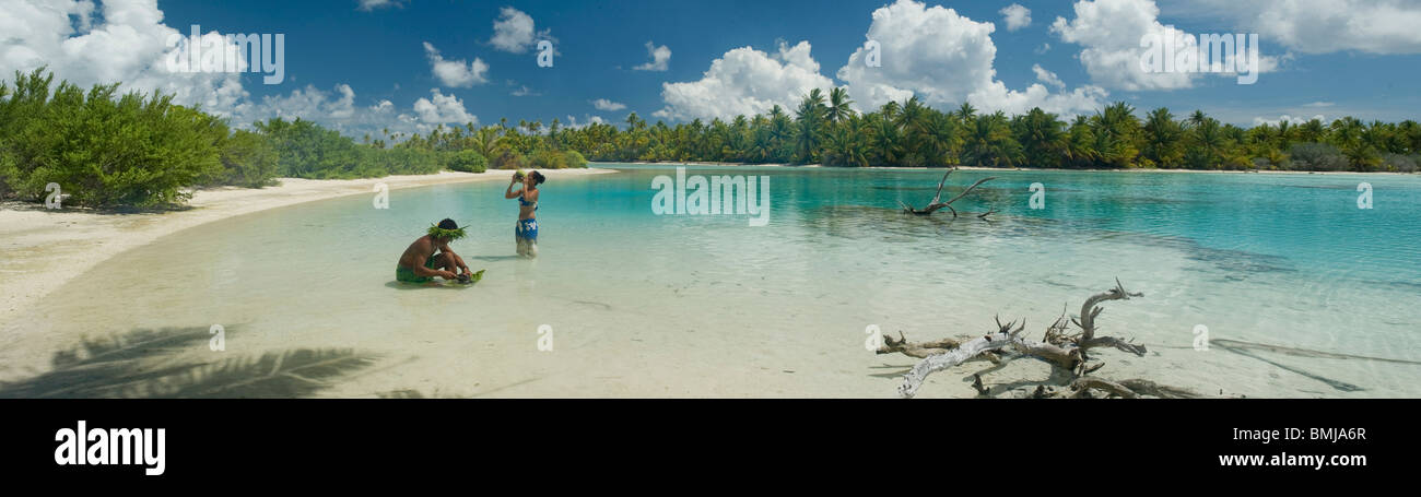 Panoramic of Fakarava lagoon. Tahitian man an woman are cooking fish and drink coconut water - Stock Image