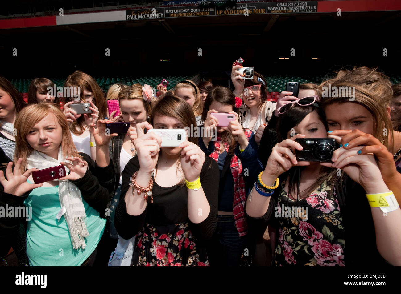 A group of teenage girls taking photos on their phones visiting the Millennium Stadium in Cardiff, the capital city - Stock Image