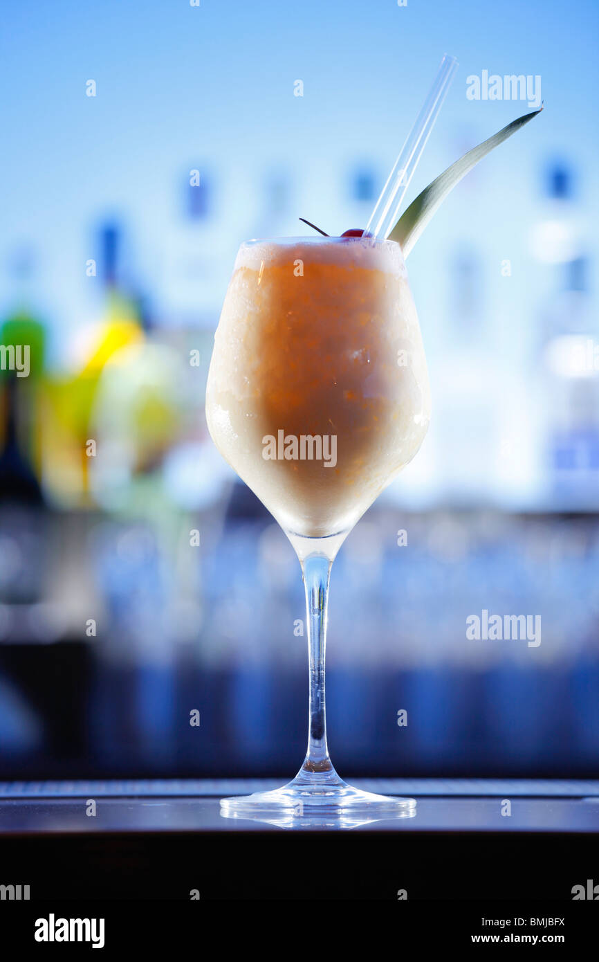 Pina Colada cocktail on a bar, blue background - Stock Image