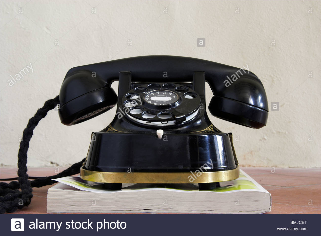 An old Bakelite telephone on a phone book directory, UK. - Stock Image