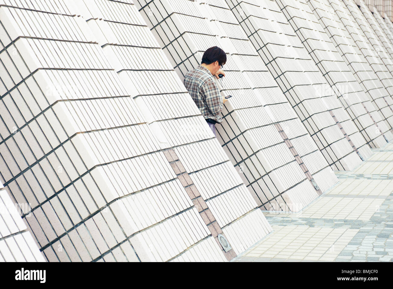 A middle aged man with glasses resting on tilted wall checking on his mobile phone while waiting for his wife outside - Stock Image