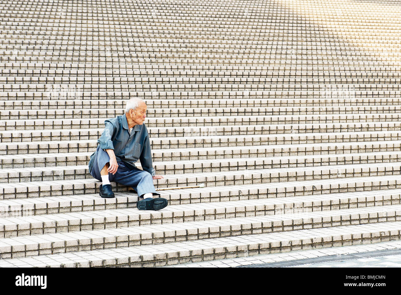 A lonely old Chinese man sits in the shade on flies of stairs outside Hong Kong Art centre, stares at void motionlessly. - Stock Image