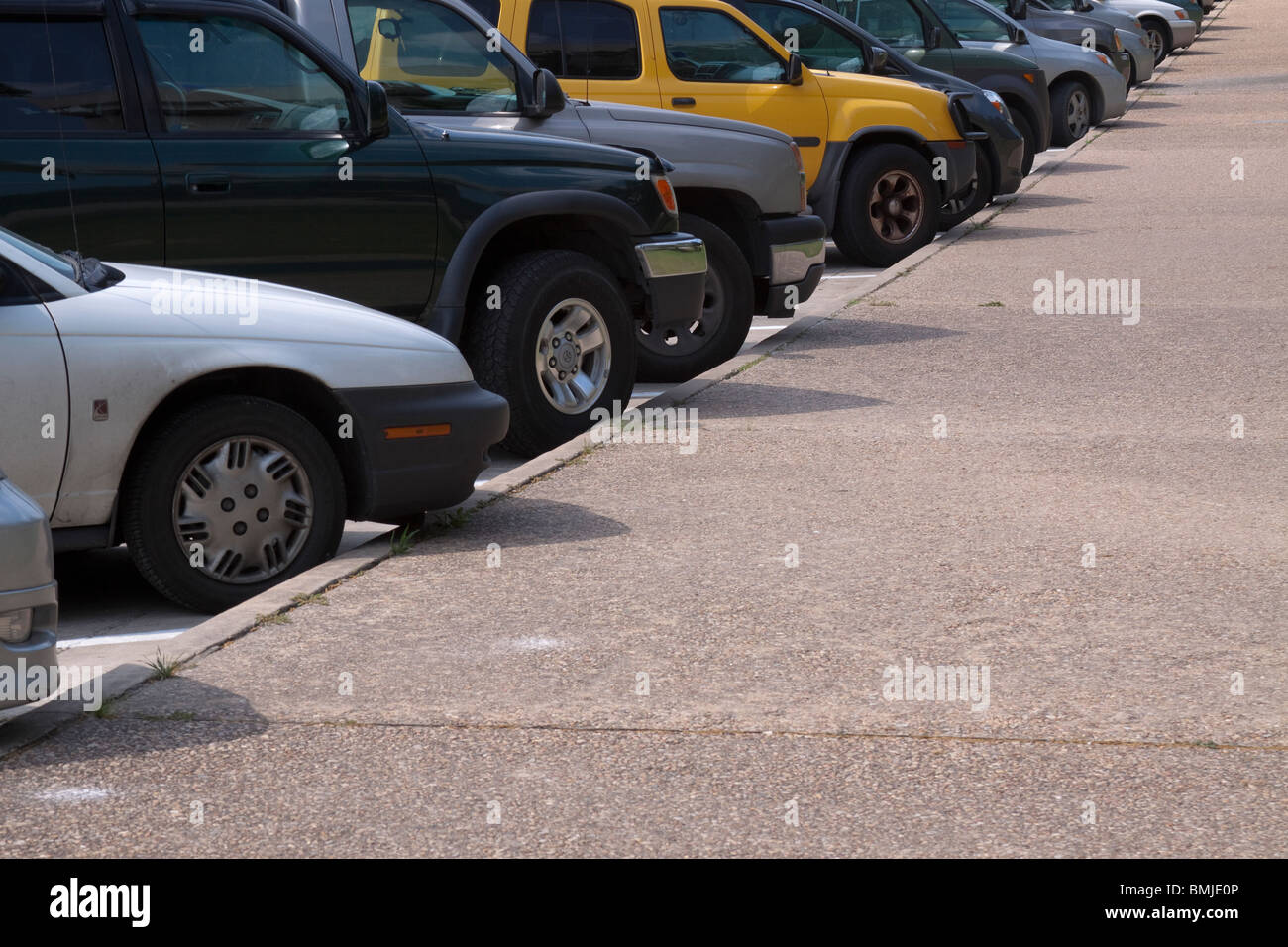 Row of cars and SUVs diagonally parked along a curb with a bright yellow SUV in the middle. - Stock Image
