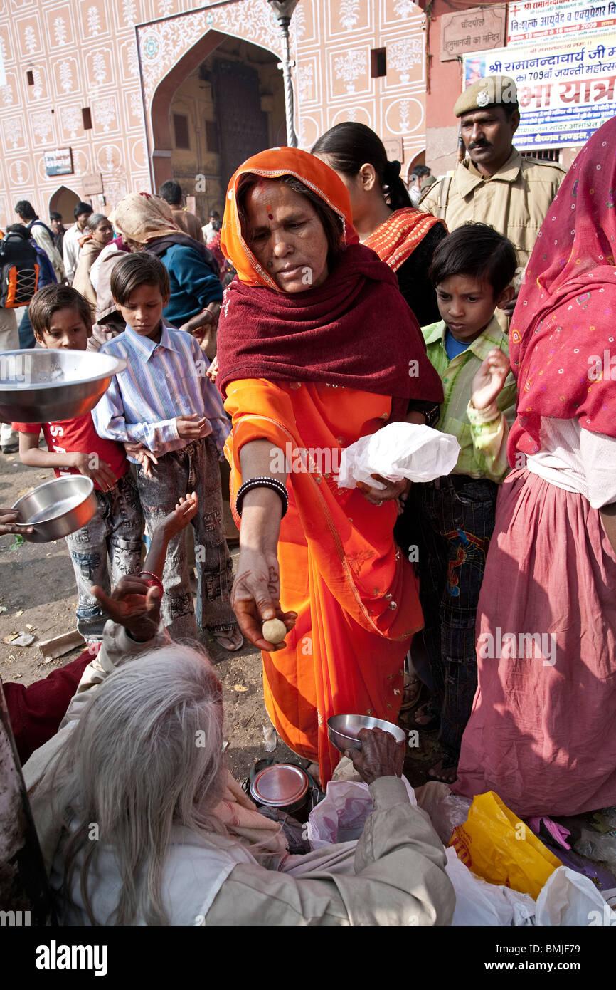 Woman giving food to beggars. Jaipur. Rajasthan. India - Stock Image