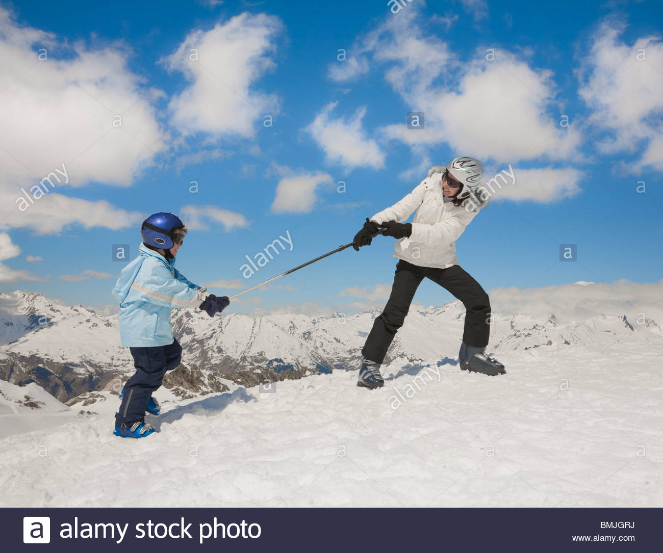 Woman pulling boy up snowy hill - Stock Image