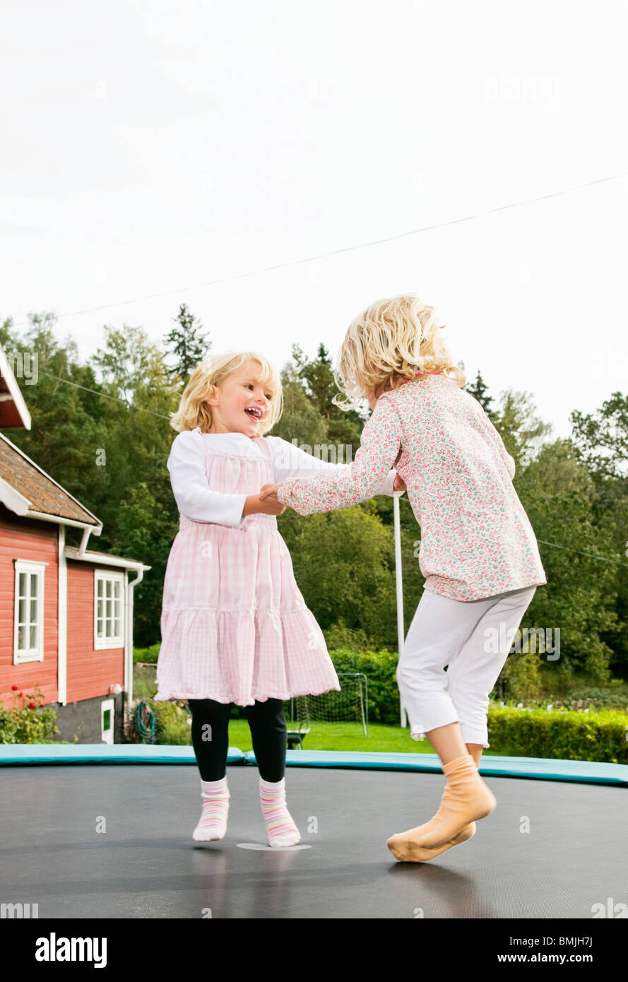 Two sisters jumping on rebouncer - Stock Image